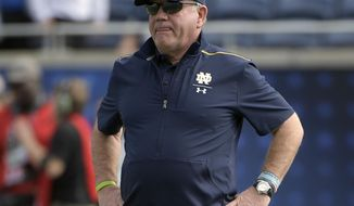 FILE - In this Dec. 28, 2019, file photo, Notre Dame head coach Brian Kelly watches warmups before the Camping World Bowl NCAA college football game against Iowa State in Orlando, Fla. Notre Dame heads to spring practice with question marks at various spots, but not at quarterback where Ian Book will be returning for the Fighting Irish. (AP Photo/Phelan M. Ebenhack, File)