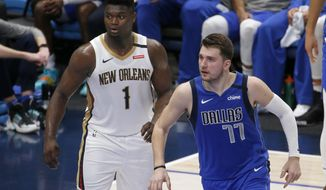 New Orleans Pelicans forward Zion Williamson (1) and Dallas Mavericks guard Luka Doncic (77) watch play during the first half of an NBA basketball game in Dallas, Wednesday, March 4, 2020. (AP Photo/Michael Ainsworth)