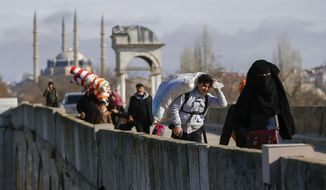 Migrants walk across a bridge in Edirne near the Turkish-Greek border on Thursday, March 5, 2020. Greece countered accusations from Turkey Wednesday that it was responsible for the death of a migrant, as its border authorities strove for a sixth day to keep thousands of migrants out by using tear gas, stun grenades and water cannons. (AP Photo/Emrah Gurel)