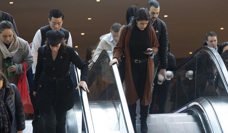 """Commuters hold on to escalator handrails as they exit the World Trade Center transportation hub, Wednesday, March 4, 2020 in New York. """"It may be possible that a person can get COVID-19 by touching a surface or object that has the virus on it and then touching their own mouth, nose, or possibly their eyes, but this is not thought to be the main way the virus spreads,"""" according to the Centers for Disease Control and Prevention (CDC). (AP Photo/Mark Lennihan)"""