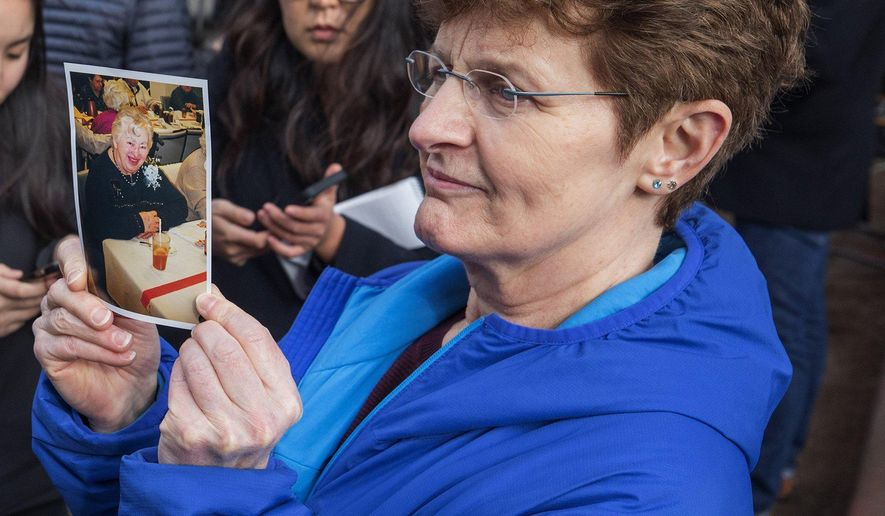Pat Herrick holds a photo of her mother, Elaine, a resident of Life Care Center who died earlier in the day, Thursday, March 5, 2020, in Kirkland, Wash. Family members of residents of the nursing home where multiple people have died from the coronavirus spoke to the media about their loved ones as Washington state authorities reported dozens more cases. (Steve Ringman/The Seattle Times via AP)