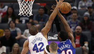 Philadelphia 76ers forward Al Horford, left, fouls Sacramento Kings forward Harrison Barnes, right, as he goes to the basket during the first quarter of an NBA basketball game in Sacramento, Calif., Thursday, March 5, 2020. (AP Photo/Rich Pedroncelli)