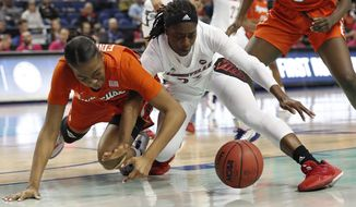 Syracuse center Amaya Finklea-Guity, left, and Louisville guard Jazmine Jones chase a loose ball during the first half of an NCAA college basketball game at the Atlantic Coast Conference women's tournament in Greensboro, N.C., Friday, March 6, 2020. (AP Photo/Gerry Broome)