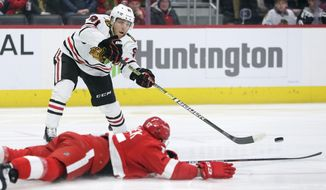 Chicago Blackhawks center Drake Caggiula (91) passes the puck against Detroit Red Wings defenseman Filip Hronek (17) during the first period of an NHL hockey game Friday, March 6, 2020, in Detroit. (AP Photo/Duane Burleson)