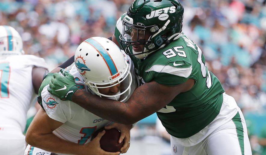 In this Nov. 3, 2019, file photo, New York Jets defensive tackle Quinnen Williams (95) sacks Miami Dolphins quarterback Ryan Fitzpatrick during the first half of an NFL football game in Miami Gardens, Fla. Williams was arrested for criminal possession of a weapon Thursday night, March 5, 2020, when he attempted to board a plane, police said in a statement. (AP Photo/Wilfredo Lee, File)