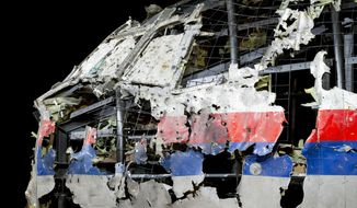 FILE - In this Tuesday, Oct. 13, 2015, file image, the reconstructed cockpit of Malaysia Airlines Flight MH17 plane is displayed before a news conference by the Dutch Safety Board in Gilze-Rijen, Netherlands. United by grief across oceans and continents, families who lost loved ones when Malaysia Airlines Flight 17 was shot down in 2014 hope that a trial starting next week will finally deliver them something that has remained elusive ever since: The truth. (AP Photo/Peter Dejong, File)
