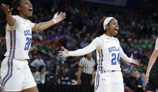 UCLA's Charisma Osborne, left, and Japreece Dean celebrate after a play against Southern California during the second half of an NCAA college basketball game in the quarterfinal round of the Pac-12 women's tournament Friday, March 6, 2020, in Las Vegas. (AP Photo/John Locher)