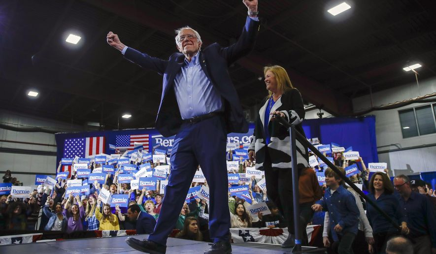 Democratic presidential candidate Sen. Bernie Sanders, I-Vt., accompanied by his wife Jane O'Meara Sanders, arrives for a primary night election rally as the crowd cheers in Essex Junction, Vt., Tuesday, March 3, 2020. (AP Photo/Matt Rourke)