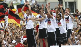 FILE - In this Sunday July 9, 2006 file photo, players of Germany's national soccer team celebrate with fans at the 'Fan Mile' in Berlin. Thousands of German soccer fans celebrate their team after Germany beat Portugal 3:1 at the third place match of the soccer World Cup on Saturday. Five years into a sprawling investigation of soccer corruption, the first courtroom trial in Switzerland is due to begin Monday, March 9, 2020 in a 2006 World Cup fraud case. Sepp Blatter, the former FIFA president, and German soccer great Franz Beckenbauer are listed by Switzerland's federal criminal court to testify in the trial of four soccer officials implicated in a suspect 6.7 million euros ($7.6 million) payment.  (AP Photo/markus Schreiber)