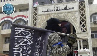 In this photo posted on the Twitter page of Syria's al-Qaida-linked Nusra Front on March 28, 2015, a fighter from Syria's al-Qaida-linked Nusra Front holds his group flag as he stands in front of the governor building in Idlib province, north Syria. Intermingled among 3 million civilians under siege in the Syrian government's assault on the last opposition stronghold are tens of thousands of al-Qaida-linked fighters and other militants who came from around the world to take part in the country's civil war. (Al-Nusra Front Twitter page via AP) **FILE**