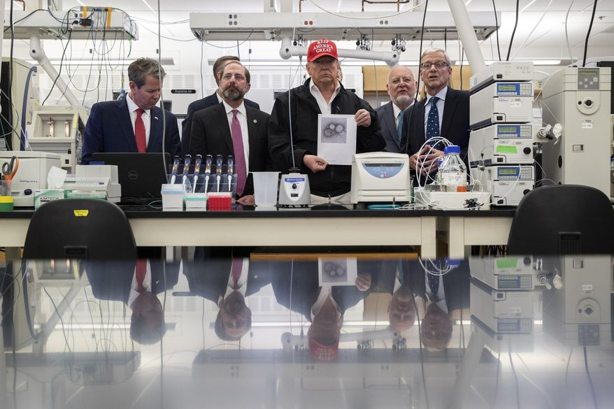 President Donald Trump holds a picture as he speaks during a meeting with Gov. Brian Kemp, R-Ga., left, Health and Human Services Secretary Alex Azar, Centers for Disease Control and Prevention Director Dr. Robert Redfield, Associate Director for Laboratory Science and Safety Steve Monroe, about the coronavirus at the Centers for Disease Control and Prevention Director, Friday, March 6, 2020 in Atlanta. (AP Photo/Alex Brandon)