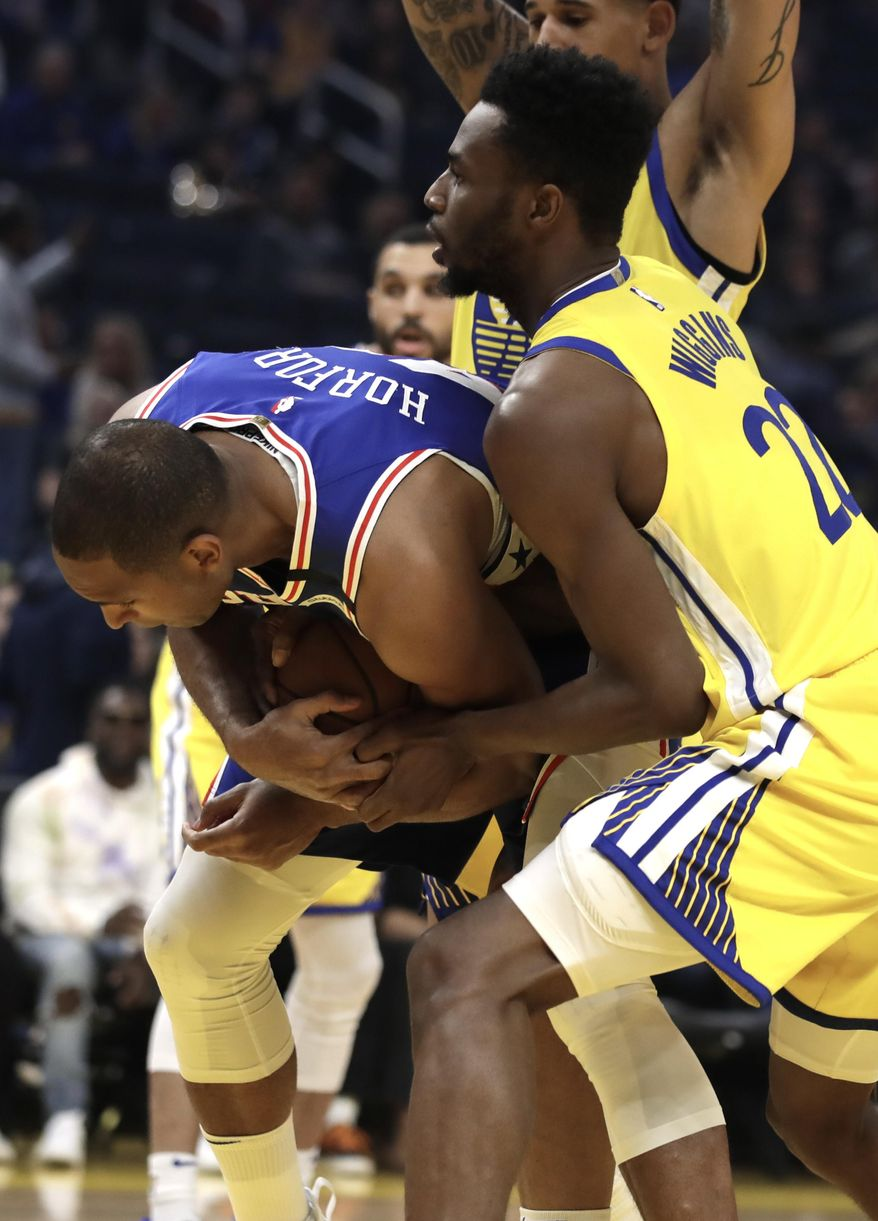 Philadelphia 76ers' Al Horford, left, keeps the ball from Golden State Warriors' Andrew Wiggins (22) in the first half of an NBA basketball game Saturday, March 7, 2020, in San Francisco. (AP Photo/Ben Margot)