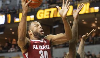 Alabama's Galin Smith, left, shoots over Missouri's Jeremiah Tilmon, left, during the first half of an NCAA college basketball game Saturday, March 7, 2020, in Columbia, Mo. (AP Photo/L.G. Patterson) ** FILE **