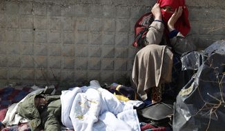 A migrant woman sits as a baby sleeps at an abandoned building in Edirne, near the Turkish-Greek border on Friday, March 6, 2020. Clashes between Greek riot police and migrants attempting to cross the border from Turkey erupted anew Friday as European Union foreign ministers held an emergency meeting to discuss the situation on the Turkey-Greece border and in Syria, where Turkish troops are fighting. (AP Photo/Darko Bandic)