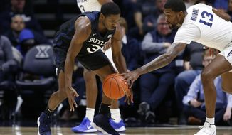 Xavier forward Naji Marshall (13) knocks the ball from the hands of Butler guard Kamar Baldwin (3) during the first half of an NCAA college basketball game, Saturday, March 7, 2020, in Cincinnati. (AP Photo/Gary Landers)
