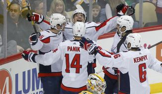 Washington Capitals' Nic Dowd, left, celebrates with teammates after scoring on Pittsburgh Penguins goaltender Matt Murray (30) during the first period of an NHL hockey game, Saturday, March 7, 2020, in Pittsburgh. (AP Photo/Keith Srakocic)