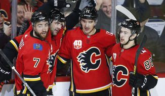 Calgary Flames' Mikael Backlund (11) celebrates his goal with teammates T. J. Brodie, (7) Mark Giordano, (5) and Andrew Mangiapane (88) during second-period NHL hockey game action against the Arizona Coyotes in Calgary, Alberta, Friday, March 6, 2020. (Jeff McIntosh/The Canadian Press via AP)