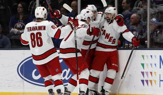 Carolina Hurricanes center Vincent Trocheck (16) celebrates with teammates center Sebastian Aho (20), right wing Andrei Svechnikov (37) and left wing Teuvo Teravainen (86), after scoring the game winning goal in overtime during an NHL hockey game against the New York Islanders, Saturday, March 7, 2020, in Uniondale, NY. (AP Photo/Jim McIsaac)