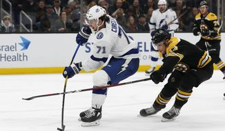 Tampa Bay Lightning's Anthony Cirelli, left, shoots while being checked by Boston Bruins' Charlie Coyle during the third period of an NHL hockey game Saturday, March 7, 2020, in Boston. (AP Photo/Winslow Townson)