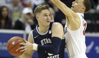 Utah State's Sam Merrill looks to pass as San Diego State's Malachi Flynn defends during the second half of an NCAA college basketball game for the Mountain West Conference men's tournament championship Saturday, March 7, 2020, in Las Vegas. (AP Photo/Isaac Brekken)