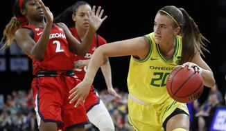 Oregon's Sabrina Ionescu (20) drives around Arizona's Aarion McDonald (2) during the second half of an NCAA college basketball game in the semifinal round of the Pac-12 women's tournament Saturday, March 7, 2020, in Las Vegas. (AP Photo/John Locher)