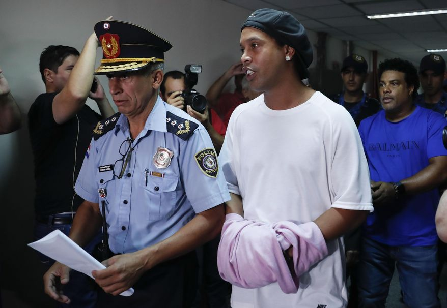 Former soccer star Ronaldinho talks as he walks escorted by Police officers with hands handcuffed to declare to judge Clara Ruiz Diaz at Justice Palace in Asuncion, Paraguay, Saturday, March 7, 2020. Ronaldinho and his brother Roberto de Assis Moreira, right back, were alleged to enter to the country with a false Paraguayan passport.(AP Photo/Jorge Saenz)