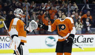Philadelphia Flyers' Carter Hart (79) and Justin Braun (61) celebrate after an NHL hockey game against the Buffalo Sabres, Saturday, March 7, 2020, in Philadelphia. Philadelphia won 3-1. (AP Photo/Matt Slocum)