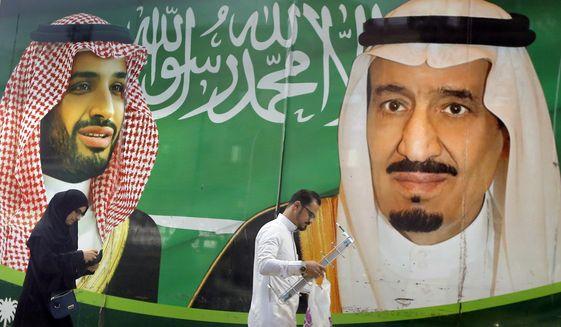 People walk past a banner showing Saudi King Salman, right, and his Crown Prince Mohammed bin Salman, outside a mall in Jiddah, Saudi Arabia, Saturday, March 7, 2020. (AP Photo/Amr Nabil)