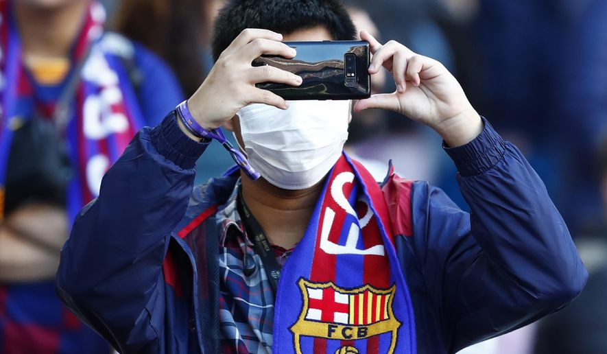 A Barcelona fan wears a face mask in an attempt to protect there self from the coronavirus uses his mobile prior a Spanish La Liga soccer match between Barcelona and Real Sociedad at the Camp Nou stadium in Barcelona, Spain, Saturday, March 7, 2020. (AP Photo/Joan Monfort)