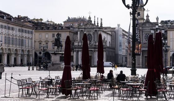 Few people sit at tables outside a bar in the center of Turin, Northern Italy, Sunday, March 8, 2020. Italy announced a sweeping quarantine early Sunday for its northern regions, igniting travel chaos as it restricted the movements of a quarter of its population in a bid to halt the new coronavirus' relentless march across Europe. (Marco Alpozzi/LaPresse via AP)