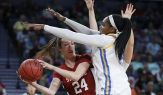 Stanford's Lacie Hull (24) passes around UCLA's Lauryn Miller, right, during the second half of an NCAA college basketball game in the semifinal round of the Pac-12 women's tournament Saturday, March 7, 2020, in Las Vegas. (AP Photo/John Locher)