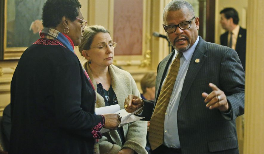 Del. Delores McQuinn, D-Richmond, left, speaks with State Sen. Siobhan Dunnavant, R-Henrico, center, and Del. Luke tori, D-Prince William, right during the House session at the Capitol Saturday March 7 , 2020, in Richmond, Va. Some of Virginia's scores of Confederate monuments could soon be removed under legislation state lawmakers approved Saturday. Del. Delores McQuinn, a Democrat from Richmond, was a sponsor of the legislation. (AP Photo/Steve Helber)