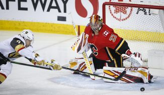 Vegas Golden Knights' William Karlsson, left, stretches to try and get the puck past Calgary Flames goalie David Rittich during the third period of an NHL hockey game in Calgary, Alberta, Sunday, March 8, 2020. (Jeff McIntosh/The Canadian Press via AP)