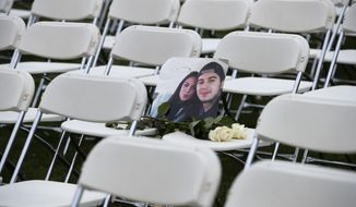 A picture of Bryce Fredriksz and his girlfriend Daisy is placed amidst 298 empty chairs, each chair for one of the 298 victims of the downed Malaysia Air flight MH17, in a park opposite the Russian embassy in The Hague, Netherlands, Sunday, March 8, 2020. A missile fired from territory controlled by pro-Russian rebels in Ukraine in 2014, tore the MH17 passenger jet apart killing all 298 people on board. United by grief across oceans and continents, families who lost loved hope that the trial which starts Monday March 9, 2020, will finally deliver them something that has remained elusive ever since: The truth. (AP Photo/Peter Dejong