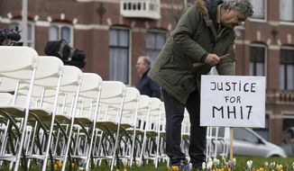 Rob Fredriksz, who lost his son Bryce and his girlfriend Daisy, places a sign next to 298 empty chairs, each chair for one of the 298 victims of the downed Malaysia Air flight MH17, placed in a park opposite the Russian embassy in The Hague, Netherlands, Sunday, March 8, 2020. A missile fired from territory controlled by pro-Russian rebels in Ukraine in 2014, tore the MH17 passenger jet apart killing all 298 people on board. United by grief across oceans and continents, families who lost loved hope that the trial which starts Monday March 9, 2020, will finally deliver them something that has remained elusive ever since: The truth. (AP Photo/Peter Dejong)