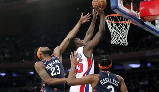 New York Knicks center Mitchell Robinson (23) defends Detroit Pistons forward Sekou Doumbouya (45) during the first half of an NBA basketball game in New York, Sunday, March 8, 2020. Knicks forward Maurice Harkless (3) watches, lower right. (AP Photo/Kathy Willens)