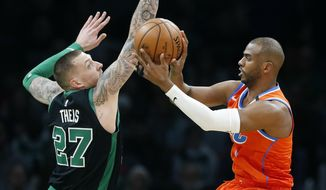 Oklahoma City Thunder's Chris Paul (3) passes the ball off against Boston Celtics' Daniel Theis (27) during the first half of an NBA basketball game, Sunday, March, 8, 2020, in Boston. (AP Photo/Michael Dwyer)