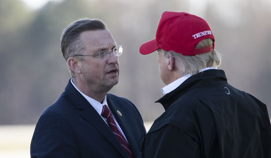 Rep. Doug Collins, R-Ga., left, greets President Donald Trump as he steps off Air Force One during arrival, Friday, March 6, 2020, at Dobbins Air Reserve Base in Marietta, Ga. (AP Photo/Alex Brandon)