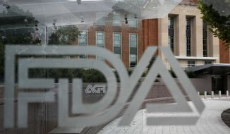 This Aug. 2, 2018, file photo shows the U.S. Food and Drug Administration building behind FDA logos at a bus stop on the agency's campus in Silver Spring, Md. U.S. regulators warned several companies to stop selling soaps, sprays and other concoctions with false claims that they can treat the new coronavirus or keep people from catching it. The warnings were emailed Friday, March 6, 2020, to companies based in the U.S., Canada and the U.K. and were announced Monday. Nearly all the targeted companies had complied by Monday morning, with mentions of the virus or products to treat it taken off their websites. (AP Photo/Jacquelyn Martin, File) **FILE**