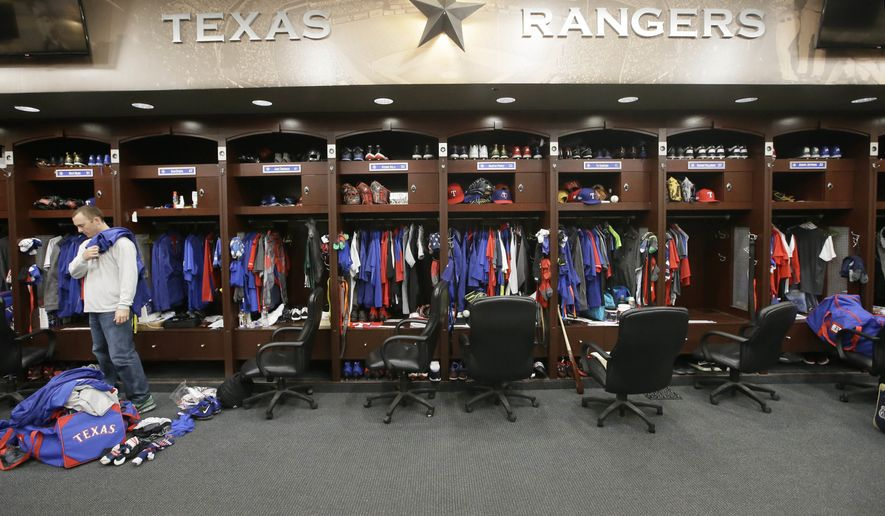 In this Oct. 11, 2016, file photo, Texas Rangers pitcher Sam Dyson, left, packs a bag in the locker room at the baseball park in Arlington, Texas. The NBA, NHL, Major League Baseball and Major League Soccer are closing access to locker rooms and clubhouses to all non-essential personnel in response to the coronavirus crisis, the leagues announced in a joint statement Monday, March 9, 2020. (AP Photo/LM Otero, File) **FILE**