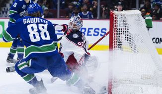 Vancouver Canucks center Adam Gaudette (88) fails to get a shot past Columbus Blue Jackets goaltender Elvis Merzlikins (90) during the second period of an NHL hockey game in Vancouver, British Columbia, Sunday, March 8, 2020. (Jonathan Hayward/The Canadian Press via AP)