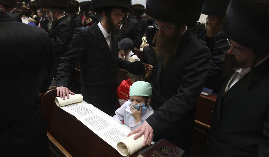CORRECTS SPELLING OF PURIM - Ultra Orthodox Jewish boy wears a doctor's costume during the first day of a Purim holiday as the Book of Esther is read in a synagogue in Bnei Brak, Israel, Monday, March 9, 2020. (AP Photo/Oded Balilty)