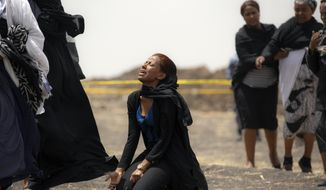 FILE - In this March 14, 2019, file photo, relatives of crash victims mourn at the scene where the Ethiopian Airlines Boeing 737 Max 8 passenger jet crashed shortly after takeoff, killing all 157 on board, near Bishoftu, in Ethiopia. The year since the crash of an Ethiopian Airlines Boeing 737 Max has been a journey through grief, anger and determination for the families of those who died, as well as having far-reaching consequences for the aeronautics industry as it brought about the grounding of all Boeing 737 Max 8 and 9 jets, which remain out of service. (AP Photo/Mulugeta Ayene, File)