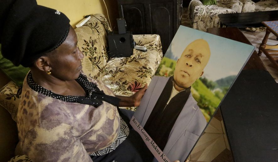In this photo taken Thursday, Feb. 27, 2020, Ruth Kageche, whose brother Rev. George Mukua Kageche, a priest based in Italy, perished on the ill-fated Ethiopian Airlines flight ET302 in 2019, holds a portrait him during an interview with The Associated Press in Nairobi, Kenya. The year since the crash of an Ethiopian Airlines Boeing 737 Max has been a journey through grief, anger and determination for the families of those who died, as well as having far-reaching consequences for the aeronautics industry as it brought about the grounding of all Boeing 737 Max 8 and 9 jets, which remain out of service. (AP Photo/Khalil Senosi)