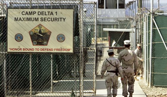 FILE - In this June 27, 2006 file photo, reviewed by a U.S. Department of Defense official, U.S. military guards walk within Camp Delta military-run prison, at the Guantanamo Bay U.S. Naval Base, Cuba. A federal judge has ordered an independent medical review for a Saudi held at the Guantanamo Bay detention center suspected of trying to take part in the Sept. 11 attacks. Lawyers for Mohammed al-Qahtani say he is mentally ill and should be returned to his homeland. Judge Rosemary Collyer's order requires two doctors from a neutral country to examine him along with a U.S. military doctor. (AP Photo/Brennan Linsley, File)
