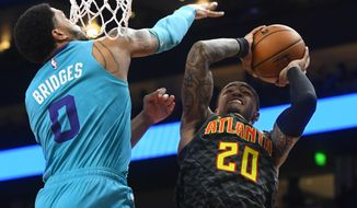Atlanta Hawks forward John Collins (20) shoots as Charlotte Hornets forward Miles Bridges defends during the first half of an NBA basketball game Monday, March 9, 2020, in Atlanta. (AP Photo/John Amis)