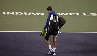FILE - In this Monday, March 11, 2019, file photo, Novak Djokovic, of Serbia, walks off the court during a rain break in his match against Philipp Kohlschreiber, of Germany, at the BNP Paribas Open tennis tournament in Indian Wells, Calif. The BNP Paribas Open tennis tournament, set to begin Wednesday, March 11, 2020, has been postponed after a case of coronavirus was confirmed in the Coachella Valley. (AP Photo/Mark J. Terrill) ** FILE **