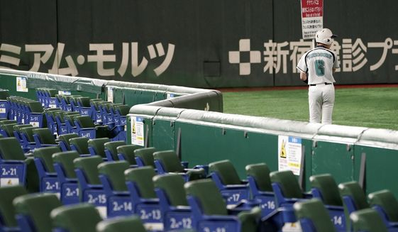 In this Feb. 29, 2020, photo, a ball boy walks with notice next to empty spectators' seats during play in a preseason baseball game between the Yomiuri Giants and the Yakult Swallows at Tokyo Dome in Tokyo. Japanese officials said Monday, March 9, 2020 they are postponing the start of the 12-team professional baseball league season because of the spread of the coronavirus. (AP Photo/Eugene Hoshiko)