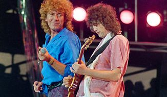 """FILE - In this July 13, 1985 file photo, Led Zeppelin bandmates, singer Robert Plant, left, and guitarist Jimmy Page, reunite to perform for the Live Aid famine relief concert at JFK Stadium in Philadelphia. From left are John Bonham, Robert Plant, Denny and Jimmy Page. A federal appeals court on Monday, March 9, 2020, restored a jury verdict that found Led Zeppelin did not steal """"Stairway to Heaven."""" (AP Photo/Amy Sancetta, File)"""