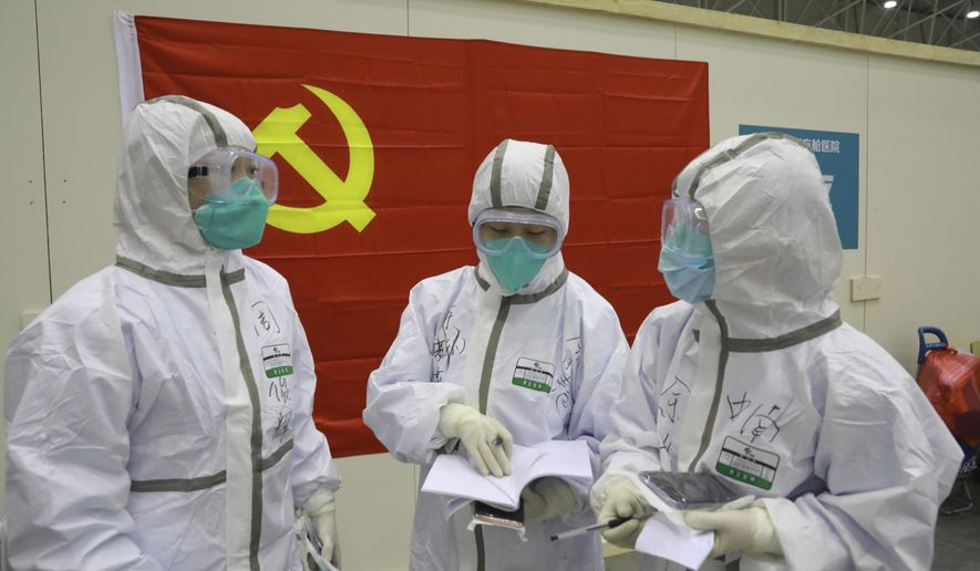 """In this photo taken Feb. 8, 2020 and released by Xinhua News Agency, medical workers discuss patients' treatment near a Communist Party flag at the """"Wuhan Living Room"""" temporary hospital in Wuhan, central China's Hubei Province. As the rest of the world grapples with a burgeoning virus outbreak, China's ruling Communist Party has turned to its propaganda playbook to portray its leader as firmly in charge, leading an army of health workers in a """"people's war"""" against the disease. (Gao Xiang/Xinhua via AP)"""